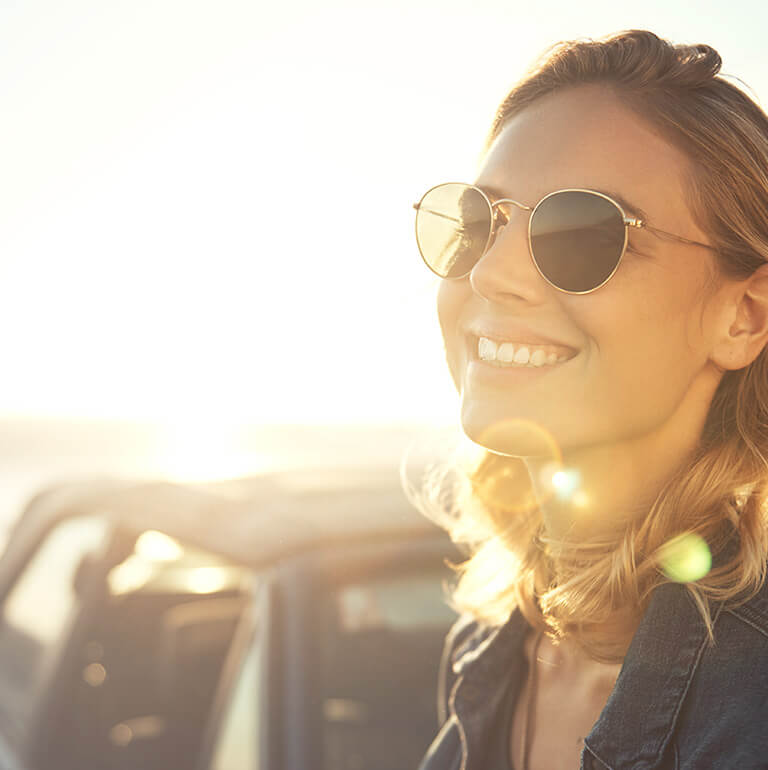 Woman smiling outside wearing sunglasses