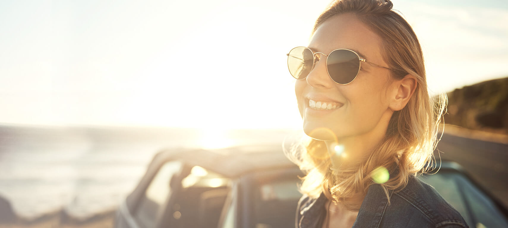 Woman wearing sunglasses smiling while the sun sets in the background